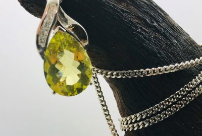 Oval shaped peridot and diamond pendant on 18ct white gold chain